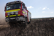 Fire brigade vehicles crossing the scorched heathland. Upton Heath, Dorset, UK.
