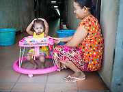 "11 JUNE 2015 - MAHACHAI, SAMUT SAKHON, THAILAND:  A Burmese migrant and her child in the hallway of a tenement building for migrant workers in Mahachai. Labor activists say there are about 200,000 migrant workers from Myanmar (Burma) employed in the fishing and seafood industry in Mahachai, a fishing port about an hour southwest of Bangkok. Since 2014, Thailand has been a Tier 3 country on the US Department of State Trafficking in Persons Report (TIPS). Tier 3 is the worst ranking, being a Tier 3 country on the list can lead to sanctions. Tier 3 countries are ""Countries whose governments do not fully comply with the minimum standards and are not making significant efforts to do so."" After being placed on the Tier 3 list, the Thai government cracked down on human trafficking and has taken steps to improve its ranking on the list. The 2015 TIPS report should be released in about two weeks. Thailand is hoping that its efforts will get it removed from Tier 3 status and promoted to Tier 2 status.       PHOTO BY JACK KURTZ"