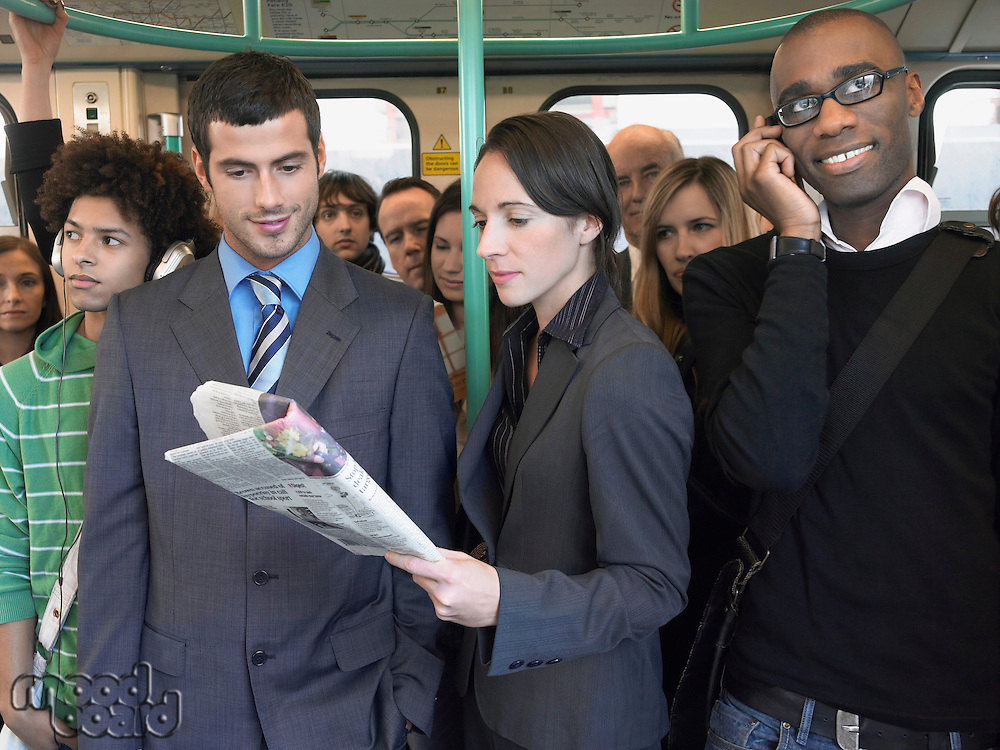 Commuters standing on train reading newspapers talking on mobiles