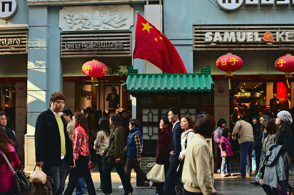 Shoppers pass by communist Chinese flag, Guangzhou, China
