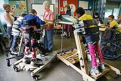 Class of physically disabled children in a special school using therapeutic equipment,