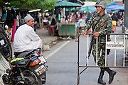 "Sept 26, 2009 -- PATTANI, THAILAND:  A Muslim man chats with a Thai soldier at a roadblock during a security operation near Krue Se Mosque in Pattani, Thailand, Sept. 26. Thailand's three southern most provinces; Yala, Pattani and Narathiwat are often called ""restive"" and a decades long Muslim insurgency has gained traction recently. Nearly 4,000 people have been killed since 2004. The three southern provinces are under emergency control and there are more than 60,000 Thai military, police and paramilitary militia forces trying to keep the peace battling insurgents who favor car bombs and assassination.   Photo by Jack Kurtz / ZUMA Press"