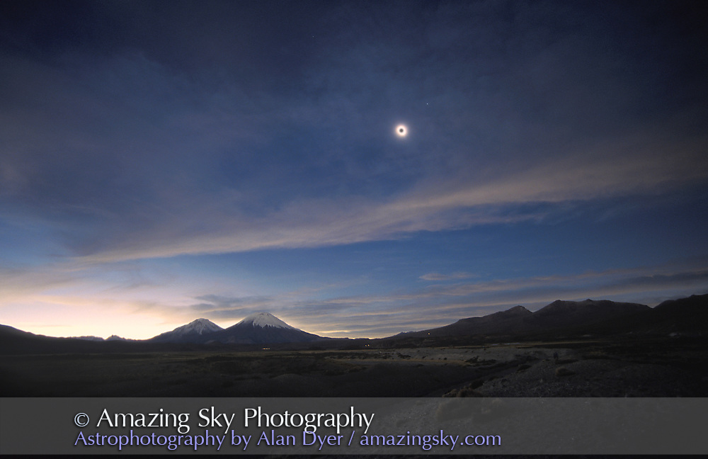 Total eclipse, Nov. 3, 1994 from Lauca National Park, northern Chile. Showing  scene in mid-totality over Parincota Volcanoes. Venus at upper right of Sun. Lunar disk added in Photoshop -- Sun was blob of light from overexposure and haze in sky. <br /> <br /> Taken wth 17mm lens on 35mm film camera. On Fuji Velvia 50 slide film.