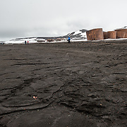 The dark, course sand of the beach at Whalers Bay on Deception Island, Antarctica. In the background are some oil tanks and buildings from the abandoned whaling station. Deception Island, in the South Shetland Islands, is a caldera of a volcano and is comprised of volcanic rock. The volcano also keeps the ground and water warmer than the surrounding area.