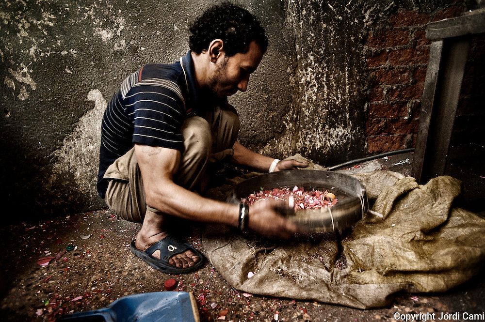 """Un joven operario """"Zabbeleen"""" criba el material con el que trabajan en un taller de Mokattam donde se clasifica y tritura diferentes tipos de plástico para reciclar. En medio del barrio de Manshiet Nasr a las afueras de El Cairo esta situado el asentamiento de Mokattam conocido como la """"Ciudad de la Basura"""" , está habitado por los Zabbaleen ,una comunidad de unos 45.000 cristianos coptos que viven desde hace varias décadas de reciclar...<br /> more »<br /> Un joven operario """"Zabbeleen"""" criba el material con el que trabajan en un taller de Mokattam donde se clasifica y tritura diferentes tipos de plástico para reciclar. En medio del barrio de Manshiet Nasr a las afueras de El Cairo esta situado el asentamiento de Mokattam conocido como la """"Ciudad de la Basura"""" , está habitado por los Zabbaleen ,una comunidad de unos 45.000 cristianos coptos que viven desde hace varias décadas de reciclar los desperdicios que genera la capital egipcia: plástico, aluminio, papel y desechos órganicos que transforman en compost . La mayoría forman parte de la Asociación para la Protección del Ambiente (APE) una ONG que actúa en el área, cuyos objetivos son proteger el medio ambiente y aumentar el sustento de las recuperadores de basura de El Cairo. Según la ONU, el trabajo que se realiza en Mokattam como uno de los diez mejores ejemplos del mundo en el mejoramiento medioambiental. El Cairo , Egipto, Junio 2011. ( Foto : Jordi Camí )"""