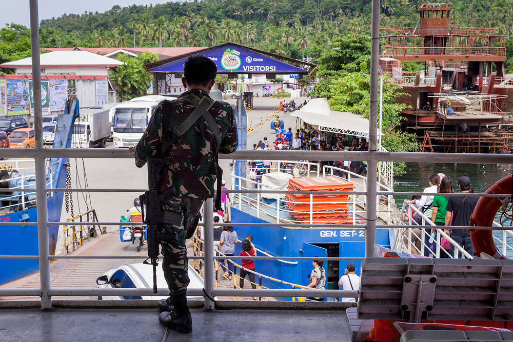 Samal Island, Mindanao, Philippines - JUNE 23: A member of the Davao Task Force monitors the Ferry Crossing into Samal Island.  On September 21, 2015, 4 people were kidnapped from the upscale Ocean View Resort Marina in Samal Island by members of the Abu Sayyaf group.  Security entering Davao City is tight since President Duterte implemented a Martial Law for 60 days in Mindanao due to the heavy fighting in Malawi 250km away.