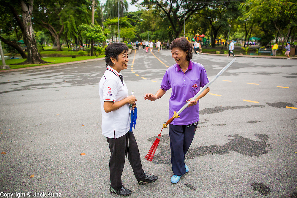 06 OCTOBER 2012 - BANGKOK, THAILAND:  Women socialize after doing Tai Chi exercises with ceremonial swords in Lumphini Park in Bangkok. The Thai government promotes exercise classes as a way staying healthy. Lumphini Park is 142 acre (57.6-hectare) park in Bangkok, Thailand. This park offers rare open public space, trees and playgrounds in the congested Thai capital. It contains an artificial lake where visitors can rent boats. Exercise classes and exercise clubs meet in the park for early morning workouts and paths around the park totalling approximately 1.55 miles (2.5 km) in length are a popular area for joggers. Cycling is only permitted during the day between the times of 5am to 3pm. Smoking is banned throughout smoking ban the park. The park was created in the 1920's and named after Lumbini, the birthplace of the Buddha in Nepal.   PHOTO BY JACK KURTZ