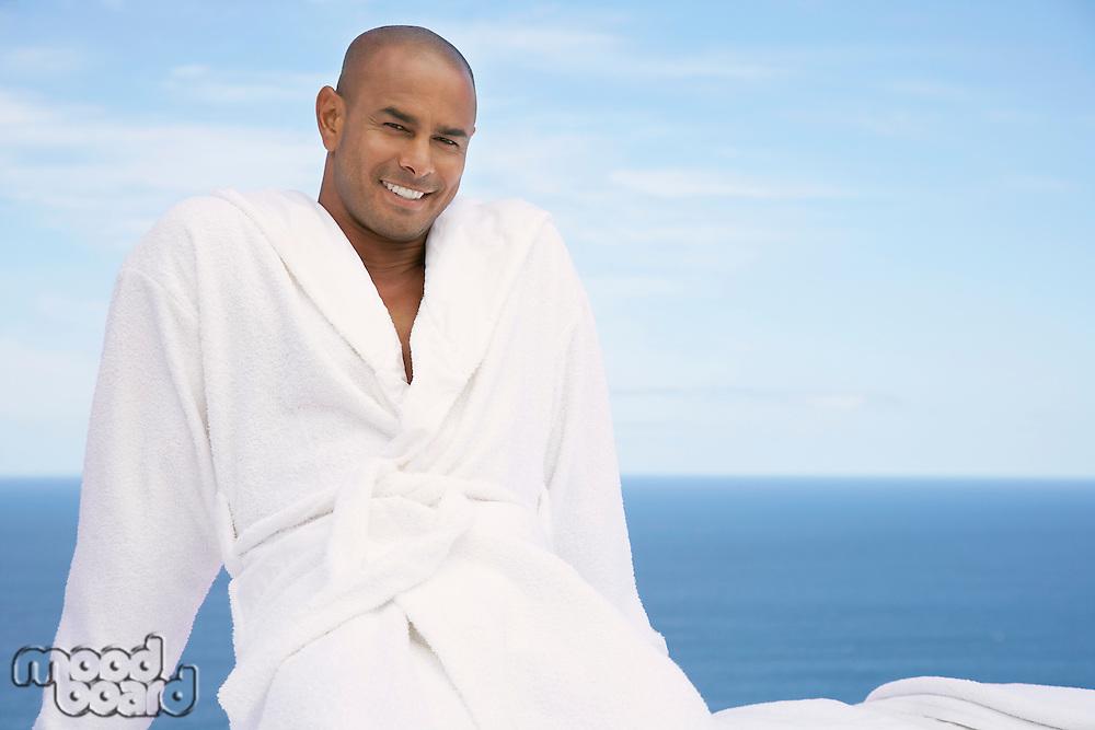 Man sitting in bathrobe smiling half length ocean behind