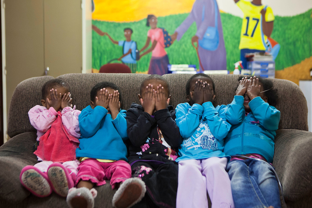A group of young girls hiding their faces from the camera and sitting on a sofa in the living room at Lambano Sanctuary, a hospice and care home for children with HIV Guateng, South Africa.