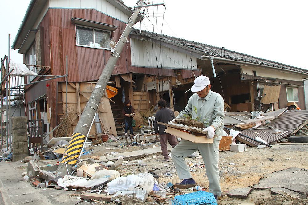 May 16, 2011; Watari, Miyagi Pref., Japan - The Shishido family rummages through what is left of their house, looking to salvage what they can after the magnitude 9.0 Great East Japan Earthquake and Tsunami that devastated the Tohoku region of Japan on March 11, 2011...They have been coming to their house almost everyday, but this was the last day they can take anything out as their house was scheduled for demolition the next day.