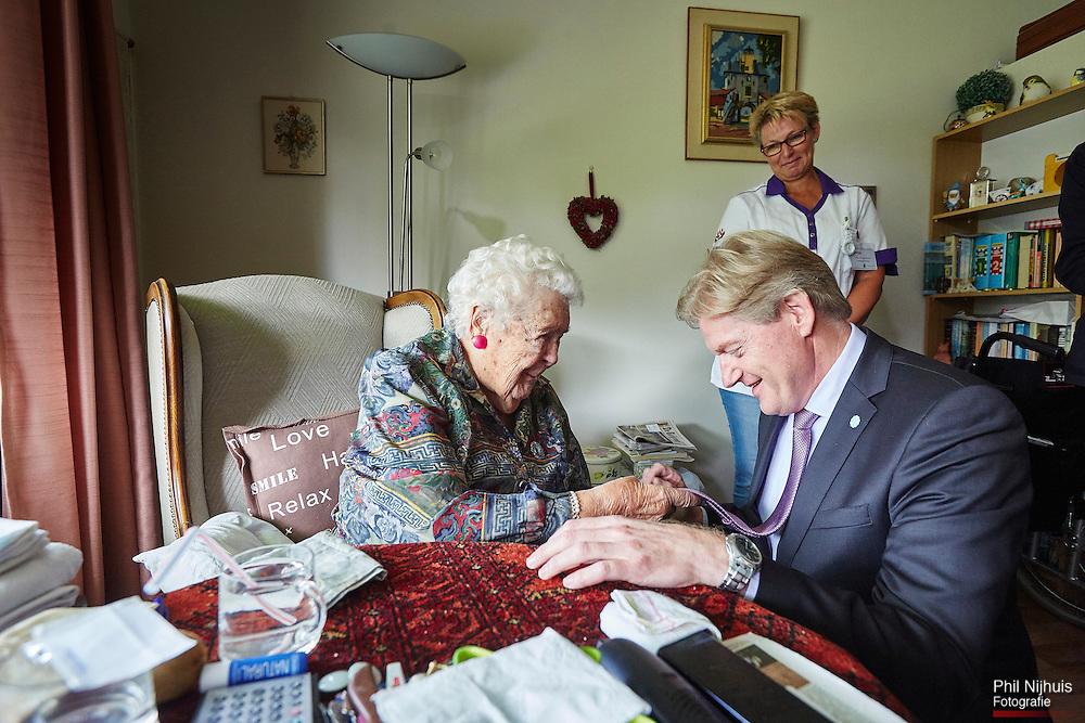 Den Haag, 22 september 2015 - Staatssecretaris van VWS, Martin van Rijn op bezoek bij een 102 jarige dame die een opmerking maakt over demonie stropdas van de minister.Foto: Phil Nijhuis