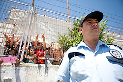 © licensed to London News Pictures. HATAY/ TURKEY. PICTURE DATED. 17/06/2011.Turkish police officer protects the Syrian refugees who are demonstrating against President Bashar al-Assad behind the walls of the Turkish Red Crescent camp in the Altinozu district of the Turkish city of Hatay, near the Syrian border, on June 17, 2011. More than 9.000 Syrians have now fled the violence of Syria's 3-month anti-regime uprising against the rule of President Bashar al-Assad and crossed into Turkey in the past ten days. Please see special instructions for usage rates. Photo credit should read TOLGA AKMEN/LNP