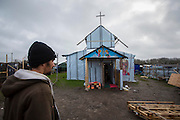 FRANCE, Calais: 18 December 2015 Fazal 25, a refugee from Afghanistan walks past the Christian Church in the refugee camp known as 'The Jungle'. The camp in Calais is now believed to hold 7,000 refugees, who are all trying to prepare for the cold winter months ahead.<br /> Rick Findler / Story Picture Agency