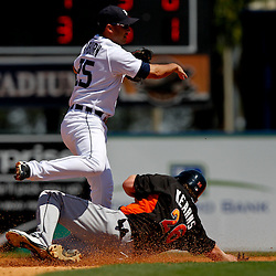 March 26, 2012; Lakeland, FL, USA; Detroit Tigers second baseman Ryan Raburn (25) turns a double play as he jumps over Miami Marlins left fielder Austin Kearns (26) during the top of the fifth inning of a spring training game at Joker Marchant Stadium. Mandatory Credit: Derick E. Hingle-US PRESSWIRE