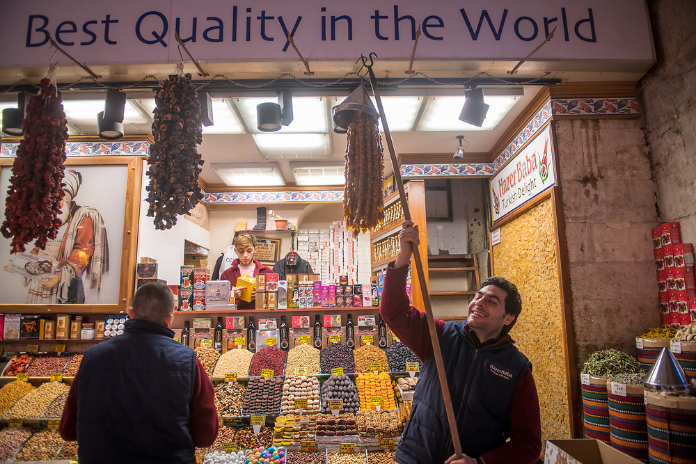 Adult male lets out of laugh while hanging sweets out in front of shop in Istanbul Spice bazaar in Turkey