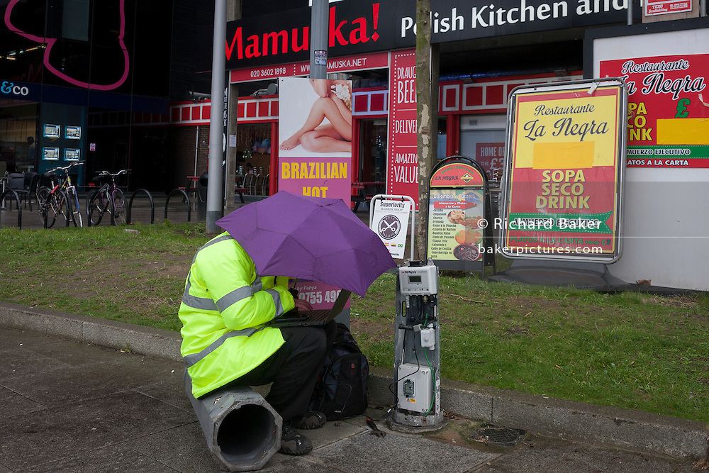An engineer attending to an ABB Aquamaster water flow meter, shelters from the rain under an umbrella, while hooked up to a laptop, on 4th January, at Elephant & Castle, London borough of Southwark, England.