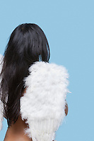 Back view of young woman wearing artificial wings over blue background
