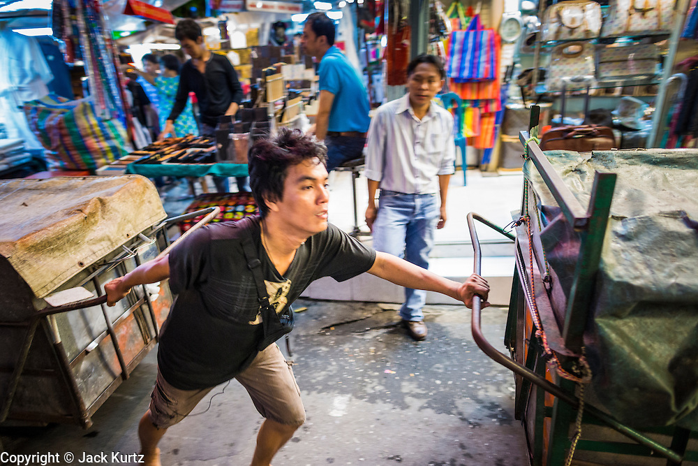 4 JUNE 2013 - BANGKOK, THAILAND:  A vendor pushes his carts of merchandise through the Patpong Night Bazaar in Bangkok. Patpong was one of Bangkok's notorious red light districts but has been made over as a night market selling clothes, watches and Thai handicrafts. The old sex oriented businesses still exist but the area is now better known for its night shopping.      PHOTO BY JACK KURTZ