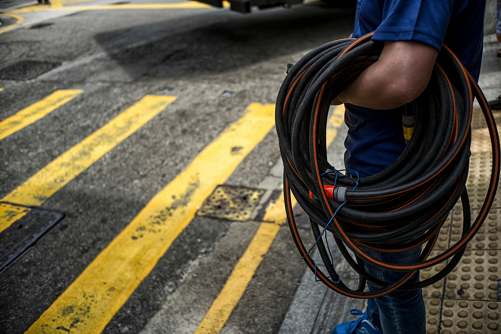 Hong Kong | 03.05.2017: Hong Kong <br /> <br /> hier: Mann mit Gartenschlauch an einem Zebrastreifen<br />  <br /> Sascha Rheker<br /> 20170503<br /> <br /> [Inhaltsveraendernde Manipulation des Fotos nur nach ausdruecklicher Genehmigung des Fotografen. Vereinbarungen ueber Abtretung von Persoenlichkeitsrechten/Model Release der abgebildeten Person/Personen liegt/liegen nicht vor.]