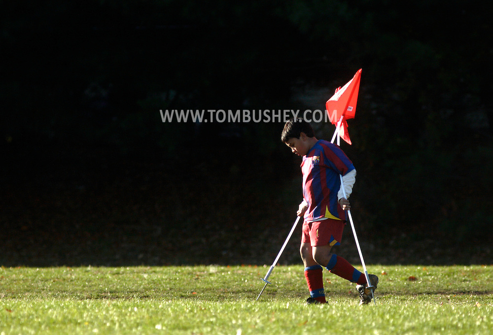 Middletown, NY - A youth soccer player carries the corner flags off the field after a game at Watts Park on Nov. 11, 2007.