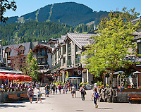 Village Square in the centre of Whistler Village is filled with people enjoying the warm summer morning.