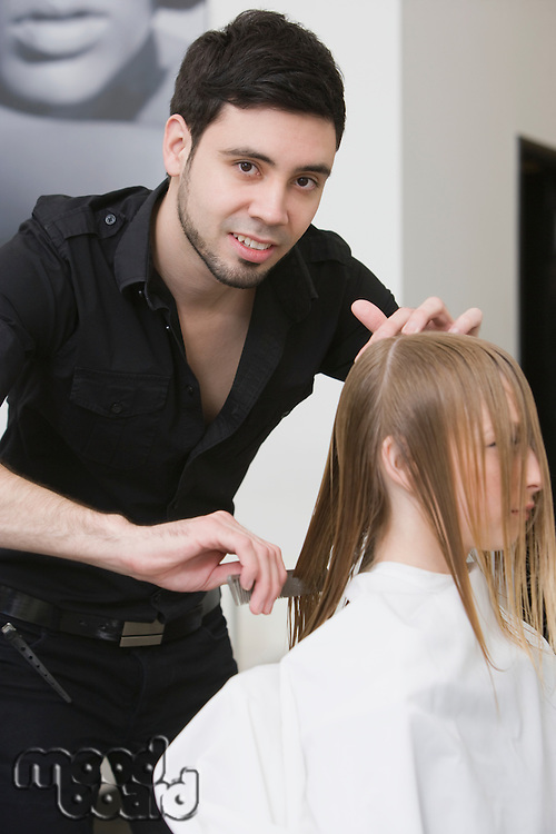 Man cutting and combing a young womans hair in the hairdressers