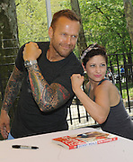 "Bob Harper, trainer on ""The Biggest Loser,"" flexes with a fan at SELF magazine's 21st annual Workout in the Park, Saturday, May 10, 2014, in New York's Central Park, where he signed copies of his newest book ""Skinny Meals."" (Photo by Diane Bondareff/Invision for SELF/AP Images)"