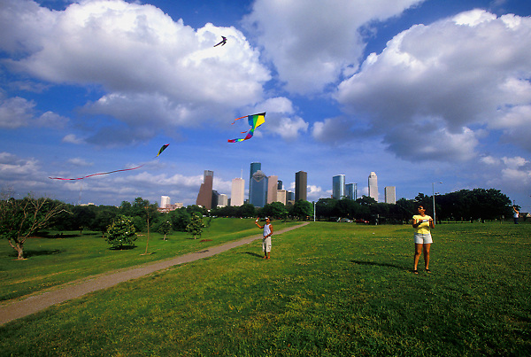 Stock photo of two people flying kites in the afternoon in the park near downtown Houston Texas