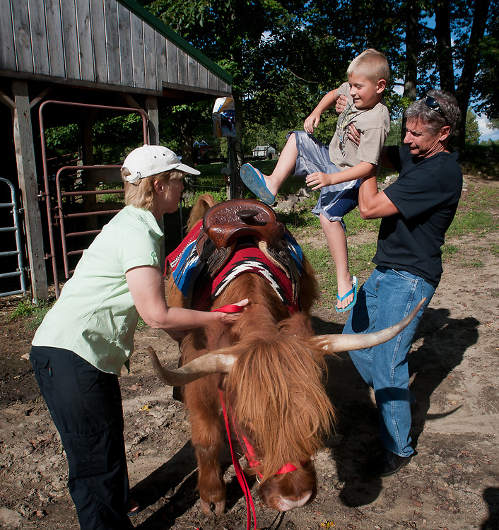 Presidential hopeful, former New Mexico Governor Gary Johnson gives Tanner McKim a hand sitting on Missy a Scottish Highlander as he pays a visit and takes a tour of Miles Smith farm in Loudon, NH. 23rd of august 2011.