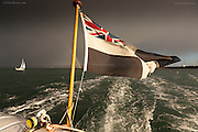 Evening sunlight catching the Cornish flag at the stern of the St Mawes Ferry having crossed the Carric Roads in windy wet weather, forming a rainbow of the St Just in Roseland headland. A sailing yacht makes it's way out past Falmouth Docks into Falmouth Bay.