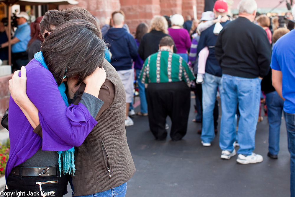 "15 JANUARY 2010 - TUCSON, AZ:    People visit the memorial for victims of the mass shooting in Tucson, AZ, Saturday, January 15, one week after the shooting. Six people were killed and 14 injured in the shooting spree at a ""Congress on Your Corner"" event hosted by Arizona Congresswoman Gabrielle Giffords at a Safeway grocery store in north Tucson on January 8. Congresswoman Giffords, the intended target of the attack, was shot in the head and seriously injured in the attack but is recovering. Doctors announced that they removed her breathing tube Saturday, one week after the attack. The alleged gunman, Jared Lee Loughner, was wrestled to the ground by bystanders when he stopped shooting to reload the Glock 19 semi-automatic pistol. Loughner is currently in federal custody at a medium security prison near Phoenix. PHOTO BY JACK KURTZ"