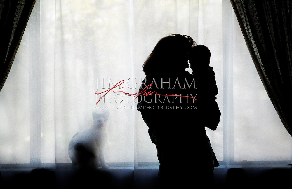 A mother holds her child while framed in light of a picture window. (Photography by Jim Graham)