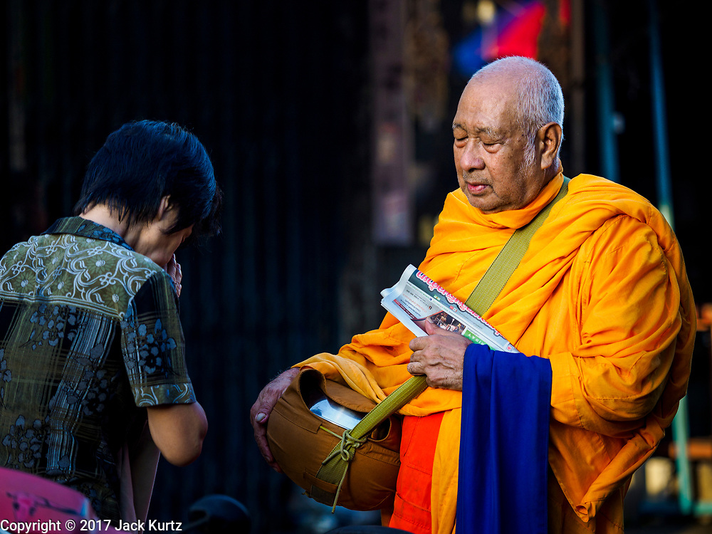 02 JUNE 2017 - BANGKOK, THAILAND:  A Buddhist monk solicits alms near the Wong Wian Yai train station in Thonburi.       PHOTO BY JACK KURTZ