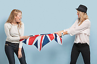 Two young women playing tug of war with British flag against light blue background