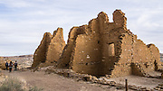 People explore the stone wall ruins of Kin Kletso Great House, in Chaco Culture National Historical Park, New Mexico, USA. Kin Kletso Great House was built around 1120-1130 AD (based on tree-ring dates) with 65 rooms and five kivas, but was abandoned by the 1150s AD. Chaco Culture National Historical Park hosts the densest and most exceptional concentration of pueblos in the American Southwest and is a UNESCO World Heritage Site. Chaco Canyon is in remote northwestern New Mexico, between Albuquerque and Farmington, USA. From 850 AD to 1250 AD, Chaco Canyon advanced then declined as a major center of culture for the Ancient Pueblo Peoples. Chacoans quarried sandstone blocks and hauled timber from great distances, assembling fifteen major complexes that remained the largest buildings in North America until the 1800s. Climate change may have led to its abandonment, beginning with a 50-year drought starting in 1130.