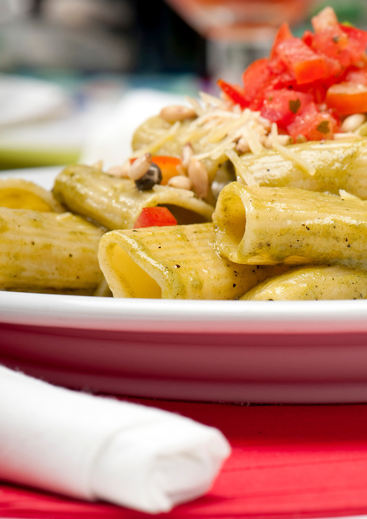 Plate of pasta salad and background, use of selective focus.