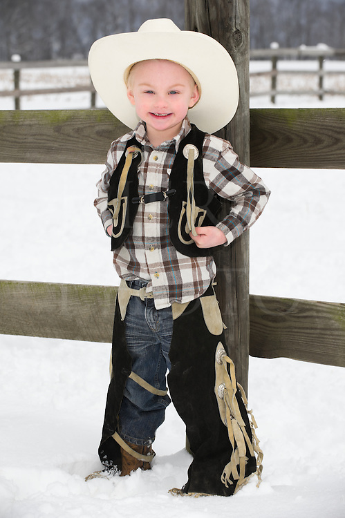 Young boy dressed as a cowboy standing outdoors at a farm fence in winter snow, casual western wear and hat, Pennsylvania, PA, USA.