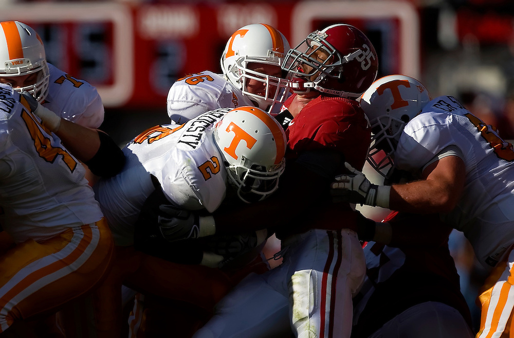 TUSCALOOSA, AL -- October, 24, 2009 -- University of Alabama linebacker Nico Johnson, center, is chocked by University of Tennessee center, Cody Sullins, center, and hit by offensive lineman Cory Sullins, right, as he tries to tackle running back Montario Hardesty during the Crimson Tide's 12-10 victory over the Volunteers at Bryant-Denny Stadium in Tuscaloosa, Ala., Saturday, Oct. 24, 2009.