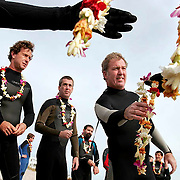 "Mourners pass out flower leis to surfers before a Paddle Out service for the untimely death of Scott Hunt in Wrightsville Beach, NC. Traditional among surfers, a ""Paddle Out"" is a memorial in which friends and fellow surfers gather in the water, where they hold hands to form a circle, offering prayers and flowers in the waves.  ltqmb  SURFERS MOURN"