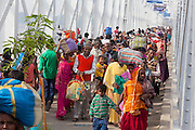 Hindu devotees are walking on the long bridge crossing the Holy Ganges River, during the yearly Sonepur Mela, Asia's largest cattle market, in Bihar, India.