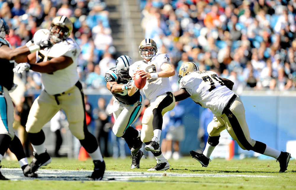 CHARLOTTE, NC - OCTOBER 19: Drew Brees #9 of the New Orleans Saints gets pressured by James Anderson of the Carolina Panthers at Bank of America on October 19, 2008 in Charlotte, North Carolina. *** Local Caption *** Drew Brees
