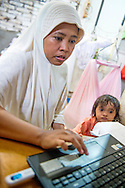 Zuhrasafita, or Ira as her friends call her, looks after her two youngest children, Jilan and Meynar as she works on a presentation for her Bachelor's degree in early education at the family home on November 24, 2014 in Banda Aceh, Indonesia. Ira's husband, Muammar, supports her studies and dream to become a kindergarten teacher. Ann Hermes/© The Christian Science Monitor 2014