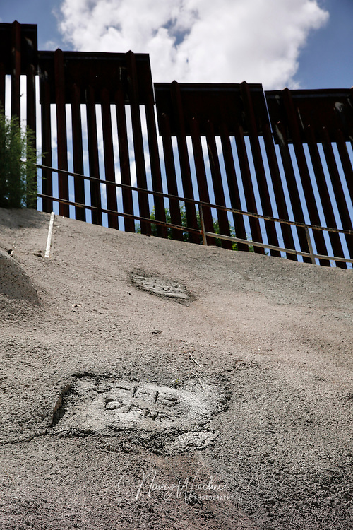 A date marks the exit of a former secret underground tunnel near the DeConcini port of entry in Nogales, Ariz. The marking was put there last year on the day U.S. Customs and Border Protection sealed the tunnel that had been used to move narcotics and people into the U.S. Seen In the background is the steel border fence. Picture taken July 16, 204. NANCY WIECHEC