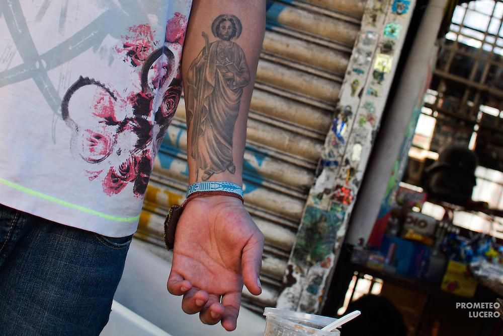 Un joven vendedor ambulante muestra su tatuaje con la imagen de San Judas en las cercanías del metro Revolución. (Prometeo Lucero)