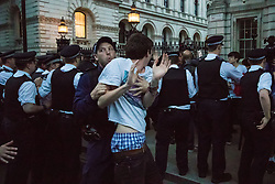 London, May 27th 2015. His jeans falling down, a protester is detained at the end of a demonstration outside Downing Street, against the Tories' ongoing campaign of austerity on the day the Queen delivered her speech to Parliament