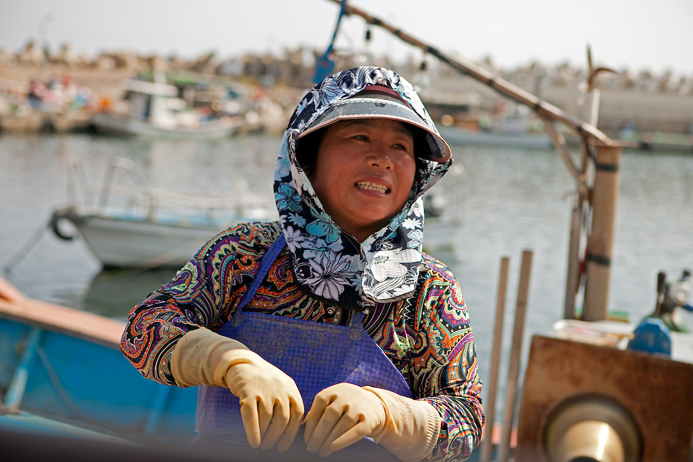 Korean fisherwoman repairing a fishing net in the village harbor Gugye-ri / South Korea, Republic of Korea, KOR, 04 October 2009.