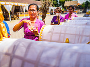 14 JULY 2016 - UBUD, BALI, INDONESIA:  A woman in Ubud prepares a coffin containing human ashes for cremation. The coffin, and nearly 100 others, will be burned in a mass cremation ceremony Saturday.  Local people in Ubud exhumed the remains of family members and burned their remains in a mass cremation ceremony Wednesday. Thursday was spent preparing for Saturday's ceremony that concludes the cremation. Almost 100 people will be cremated and laid to rest in the largest mass cremation in Bali in years this week. Most of the people on Bali are Hindus. Traditional cremations in Bali are very expensive, so communities usually hold one mass cremation approximately every five years. The cremation in Ubud will conclude Saturday, with a large community ceremony.    PHOTO BY JACK KURTZ