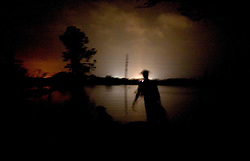 25 Sept, 2005. Cameron, Louisiana. Hurricane Rita aftermath. <br /> Local man Aaron Stokes and his dog Maggie walks into the flooded darkness in Carlyss with a can of gasoline for his boat.<br /> Photo; &copy;Charlie Varley/varleypix.com