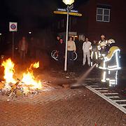 Vreugdevuur op straat Akkerweg Huizen.buitenbrand, publiek, oude en nieuw, oudjaar, nieuwjaar, brandweer, slang, spuiten, publiek, wegdek