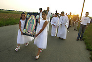 "HAMMONTON, NJ - AUGUST 19:  Dianne Castaneda (L), nine-years-old, and her sister Jazzalyn (C), eleven-years-old, carry a portrait of ""Our Lady of Guadalupe"" during a procession leading to a Catholic mass, in a farm building, August 19, 2002, in Hammonton, New Jersey. Nearly 10,000 Mexican farm workers leave their homes to labor in the fields of South Jersey annually to harvest fresh vegetables. Farm workers labor from sunrise until dusk, harvesting, cultivating and packaging produce for fresh market sale with little time for anything else. The Diocese of Camden celebrates Mass in the fields to serve as ""a spiritual outreach"" to the farm workers and their children. (Photo by William Thomas Cain/Getty Images)"